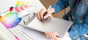 young woman artist in jeans jacket drawing something on graphic tablet at the office